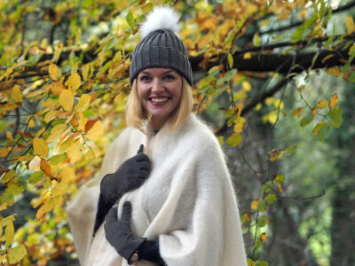 Model wearing mohair jumper and serape stood under a tree wearing woolly hat and gloves